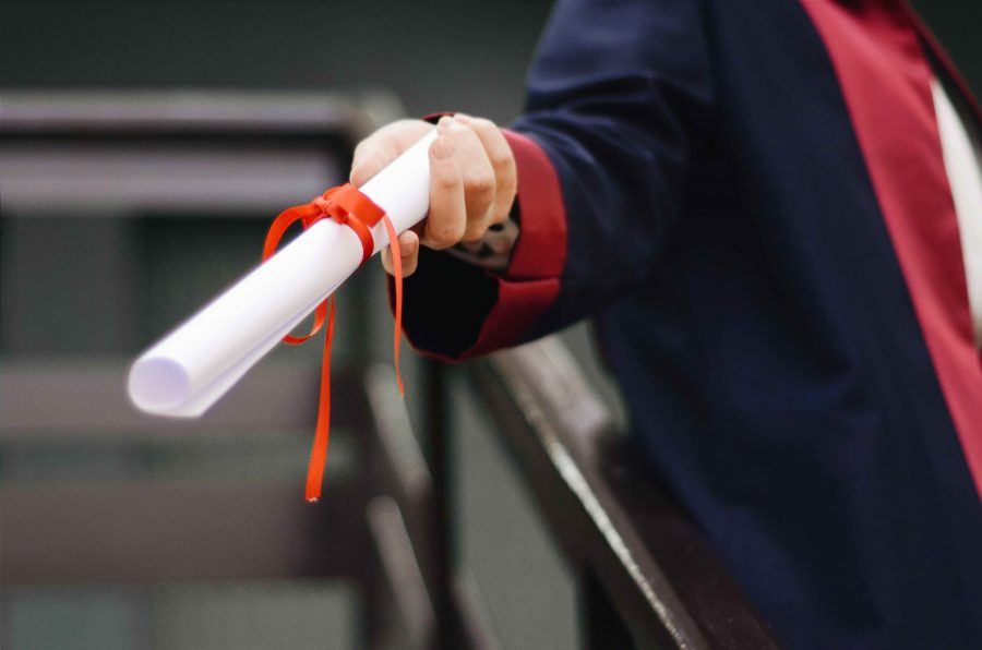 rolled diploma in hand